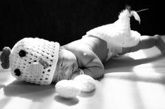聚焦在有服装鸡的亚裔新出生的女婴用在窗口旁边的两个鸡蛋与阳光 库存照片