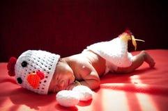 聚焦在有服装鸡的亚裔新出生的女婴用在窗口旁边的两个鸡蛋与阳光 免版税图库摄影