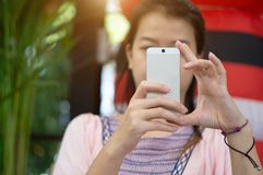 聚焦年轻亚裔妇女感人的智能手机的手 免版税库存照片