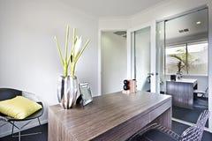 聚焦木桌和花梢项目的现代工作地点 免版税库存图片