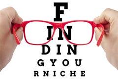 聚焦红色的眼镜发现您的适当位置 图库摄影