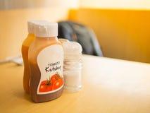 聚焦西红柿酱射击在塑料瓶、盐和胡椒的 免版税库存图片