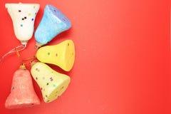 聚苯乙烯泡沫塑料响铃五个片断在红色背景的装饰的 免版税库存照片