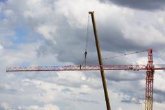 聚集在剧烈的多云背景的起重机 高度塔吊 库存照片