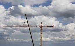 聚集在剧烈的多云背景的起重机 高度塔吊 免版税库存图片