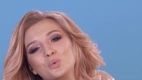 聪慧和美丽的金发碧眼的女人送一个亲吻到照相机 做广告的时尚摄影在蓝色的演播室 股票录像