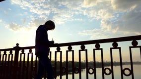 聪慧的人在河桥梁站立并且写他的想法下来在日落 股票录像