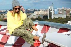 聪慧的偶然行家的魅力时髦的性感的美丽的年轻白肤金发的式样女孩在都市landskape后穿衣 库存照片