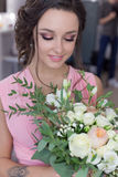 聪慧美丽的甜女孩的女傧相为一个朋友的婚礼做准备桃红色晚礼服的与晚上发型和 免版税库存图片