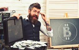 聪明和富有 商人在服务器屋子里 有现金金钱的有胡子的人 有bitcoin标志的有胡子的行家和 库存照片