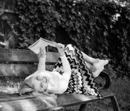 聪明和相当 聪明夫人放松 女孩放置放松与书,绿色自然背景的长凳公园 妇女花费 库存图片