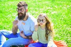 聪明和聪明的概念 爸爸和女儿坐草在grassplot,绿色背景 摆在与的孩子和父亲 库存图片