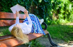 聪明夫人放松 女孩放置放松与书,绿色自然背景的长凳公园 妇女花费与书的休闲 免版税库存图片