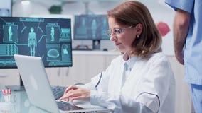 聪明女人研究员在膝上型计算机的戴着眼镜类型 股票视频
