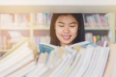 聪明的亚洲学生读书和做研究画象对c 免版税库存照片