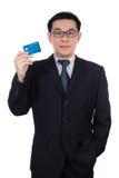聪明的亚裔中国人佩带的衣服和拿着信用卡 库存图片