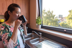 聪明的亚裔妇女在厨房里 免版税库存图片