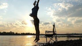 聪明的人在水坐河岸,写,并且保留他的脚在Slo Mo 股票视频