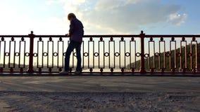 聪明的人在河桥梁站立并且投入他的想法下来在日落 股票录像