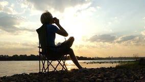 聪明的人坐,认为,喝咖啡,在河岸在日落在slo mo 股票视频