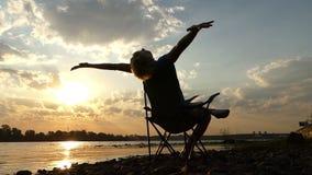 聪明的人坐,读,做在河岸的一锻炼在日落 影视素材