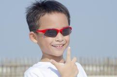 聪明的在天空的男孩佩带的太阳镜 免版税库存照片