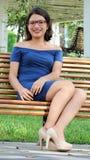 聪明的女孩坐长凳 免版税图库摄影