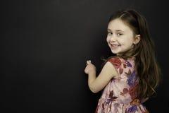 聪明的女孩突出在黑板的文字 免版税图库摄影