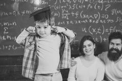 聪明的子项 神童概念 聪明的孩子,毕业生盖帽的神童指向他的头的 父母听他们 免版税库存照片
