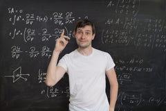 年轻聪明的学生有一个想法如何解决困难的数学问题 在黑板的算术惯例在背景中 图库摄影