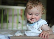 聪明的孩子坐一张床在一间明亮的屋子 免版税库存照片