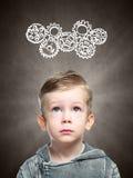 聪明的孩子认为看齿轮 图库摄影