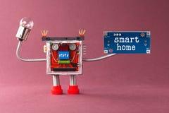 聪明的家庭机器人自动化概念 有电灯泡灯、蓝色电路板和消息的五颜六色的机械玩具 免版税库存照片