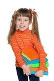 聪明的小女孩拿着书 免版税图库摄影