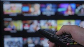 聪明的电视 网上录影放出的服务 使用应用程序和手 遥远男性手的藏品控制转动聪明的电视 股票录像