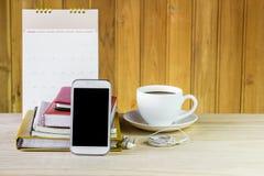 聪明的电话、咖啡杯和堆与日历的书在木 免版税库存照片