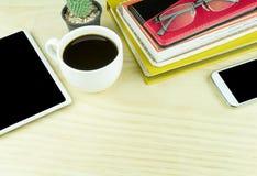 聪明的电话、咖啡杯和堆在木桌上的书 库存图片