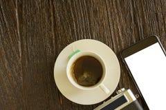 聪明的电话和照相机用热的茶在木桌上 库存图片