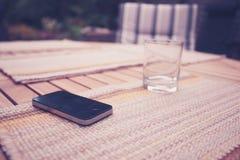 聪明的电话和玻璃在桌上 免版税库存图片