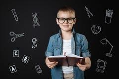 聪明的男孩佩带的玻璃和假装对大老师 免版税库存照片
