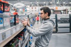 聪明的男性顾客买的汽车电池n汽车超级市场 免版税库存图片