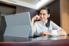 聪明的确信的微笑的女商人坐便携式计算机工作 库存照片