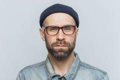 聪明的确信的时髦的人和髭,严肃神色照片有黑暗的厚实的胡子的入照相机,摆在反对灰色stu 库存图片