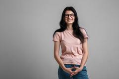 聪明的美丽的深色的女孩画象镜片的有自然构成的,在灰色背景 免版税图库摄影