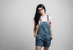 聪明的美丽的深色的女孩画象镜片的有自然构成的,在灰色背景 库存照片