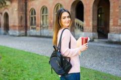聪明的聪明的研究生玻璃确信愉快在有袋子的大学庭院和书喝咖啡户外 库存图片