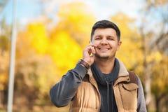 聪明的英俊的人谈话在智能手机在公园 免版税库存照片