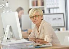 聪明的资深女实业家在办公室 库存图片