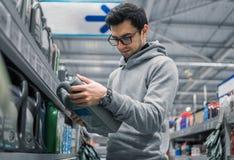 聪明的顾客买的引擎润滑油在汽车超级市场 免版税库存照片