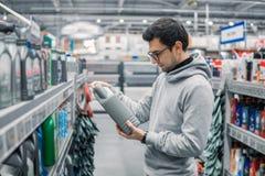 聪明的顾客买的引擎润滑油在汽车超级市场 免版税库存图片